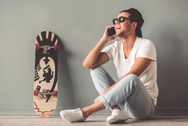 Homem de boné e óculos de sol está falando no telefone celular