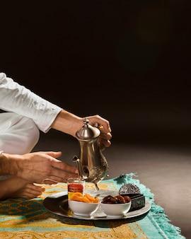 Homem de branco, derramando chá em copo pequeno vista frontal