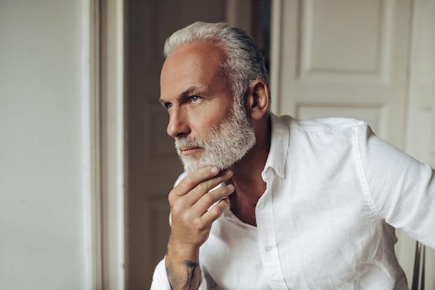 Homem de cabelo branco e camisa posando pensativamente em apartamento claro