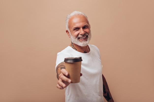 Homem de cabelo branco em poses de camiseta com uma xícara de chá
