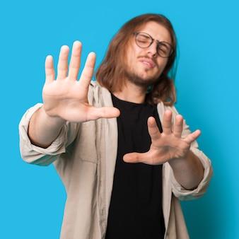 Homem de cabelo comprido com barba e óculos recusando algo na parede azul de um estúdio