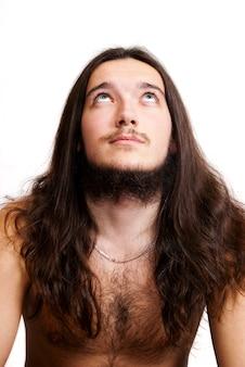 Homem de cabelo comprido e barbudo olhando para cima