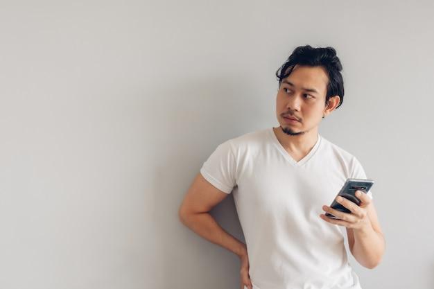 Homem de cabelo comprido em uma camiseta branca casual está usando o smartphone.