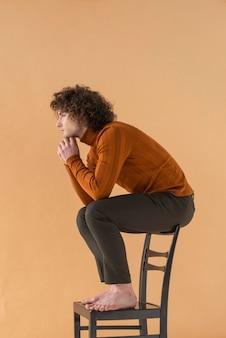 Homem de cabelo encaracolado com blusa marrom posando na cadeira