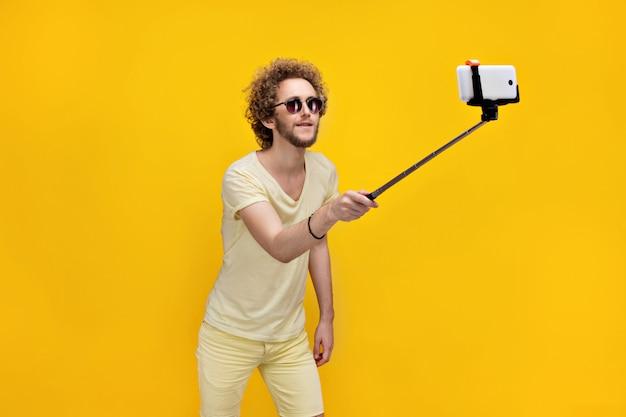 Homem de cabelo encaracolado elegante tomando selfie com monopé