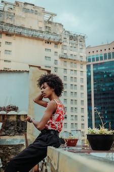 Homem de cabelo encaracolado no telhado de um edifício