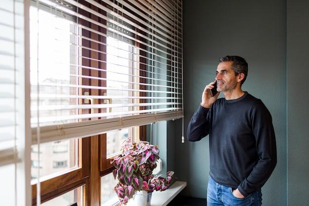 Homem de cabelo grisalho falando ao telefone enquanto olha pela janela de sua casa