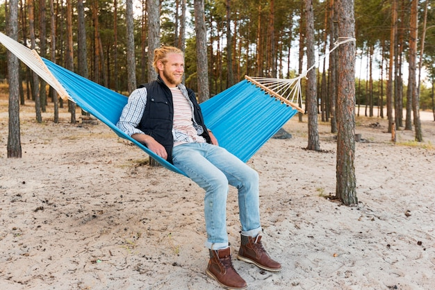 Homem de cabelo loiro sentado na rede