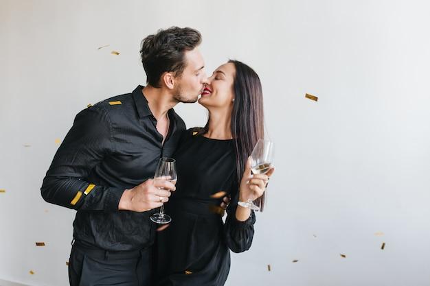 Homem de cabelo preto em uma camisa estilosa beijando sua esposa