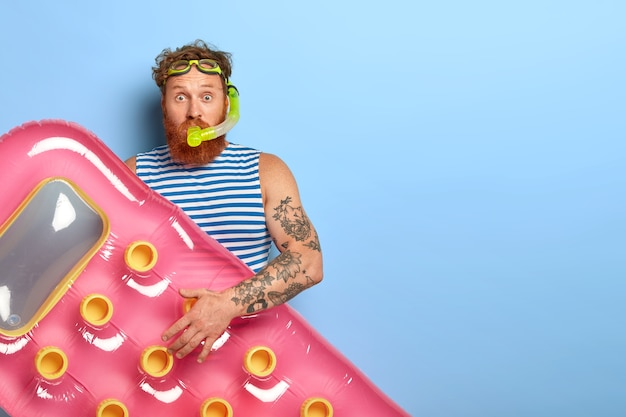 Homem de cabelo ruivo cacheado usa óculos de natação, máscara de mergulho e colchão inflado rosa, pronto para mergulhar na água do mar, usa colete listrado azul e branco