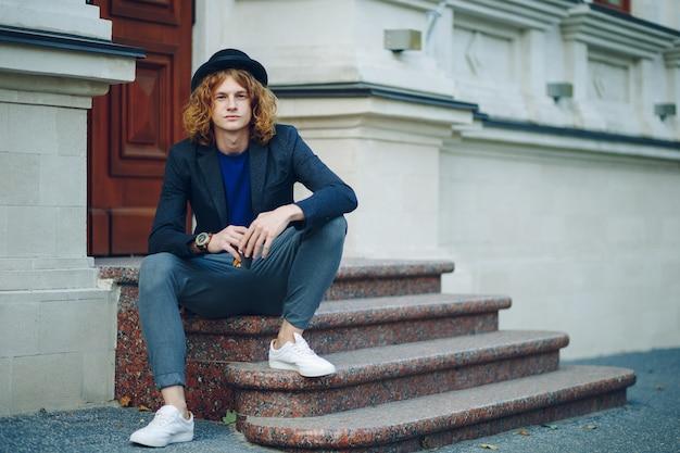 Homem de cabelo vermelho hipster sentado na escada pensando