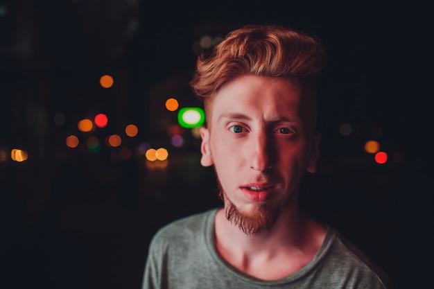 Homem de cabelo vermelho novo no fundo preto da noite. luzes da cidade à noite. no modelo cai a luz da publicidade ao ar livre
