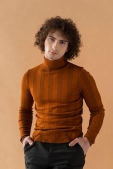 Homem de cabelos cacheados com blusa marrom posando