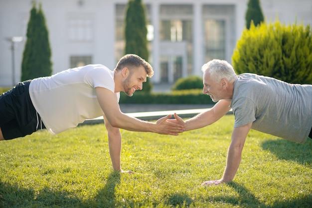Homem de cabelos castanhos e homem de cabelos grisalhos em pé na prancha na grama, apertando as mãos