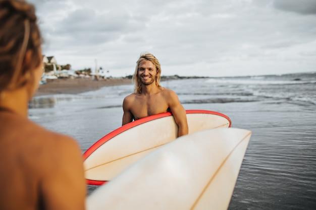 Homem de cabelos compridos com sorriso olha para a garota. casal vai surfar
