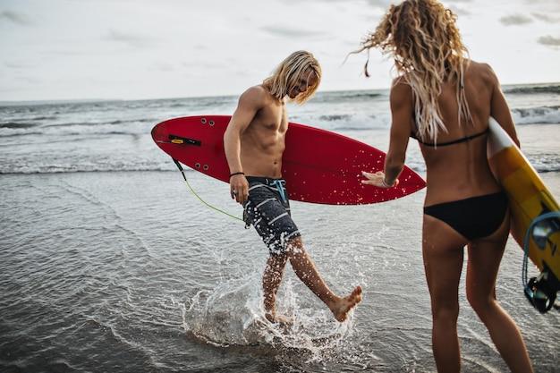 Homem de cabelos compridos e short segurando uma prancha de surf vermelha e jogando água do mar na namorada