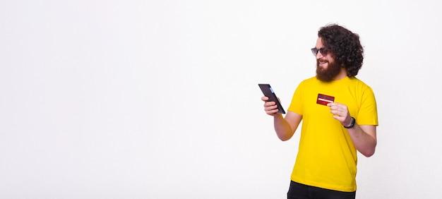 Homem de cabelos compridos, usando óculos escuros e segurando um telefone e um cartão está posando sobre fundo branco.