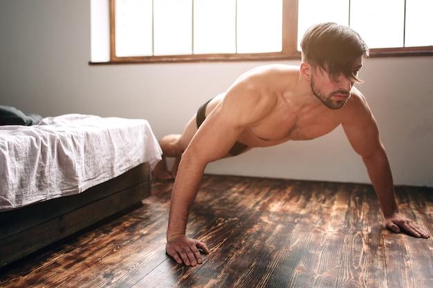 Homem de cabelos escuros barbudo nu fazendo exercícios de flexão de manhã em casa.