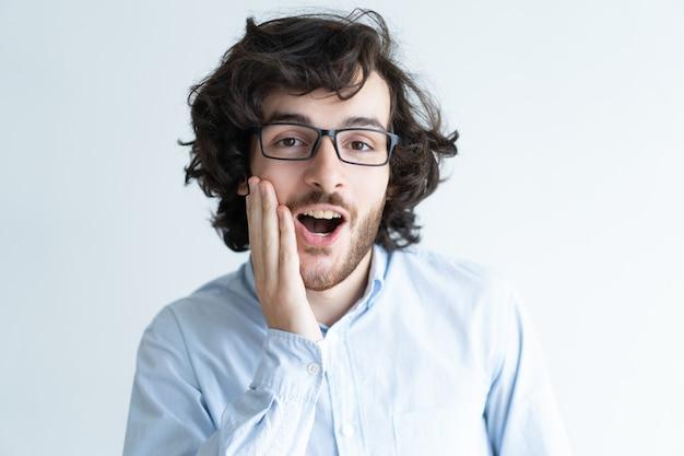 Homem de cabelos escuros chocado tocando a bochecha com a boca aberta