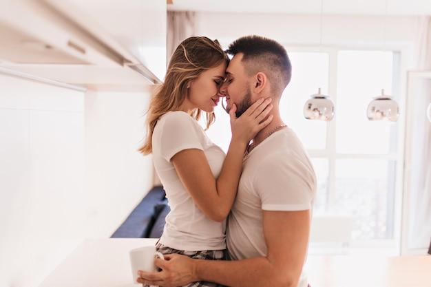 Homem de cabelos escuros desportivo segurando uma xícara de chá e abraçando a esposa. menina encantadora em traje branco tocando suavemente o rosto do namorado.