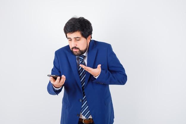 Homem de cabelos escuros em camisa branca, jaqueta azul escura, gravata olhando para o telefone e parecendo indefeso, vista frontal.