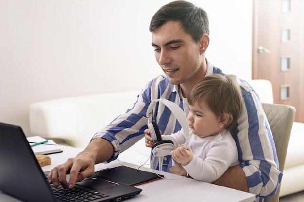 Homem de cabelos escuros em camisa listrada com bebê no colo, trabalho remoto em quarentena, ouvindo música com fones de ouvido, trabalho seguro em casa, conceito de paternidade feliz
