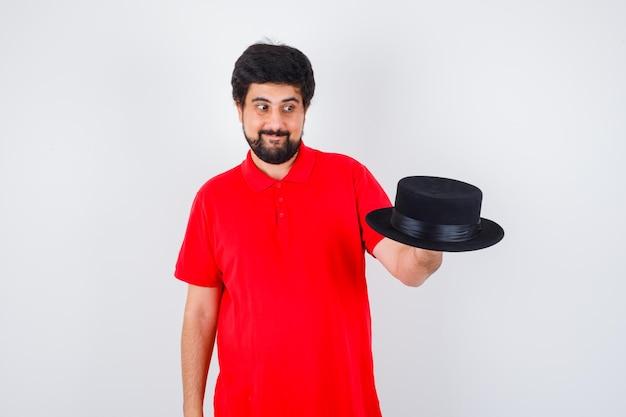 Homem de cabelos escuros em t-shirt vermelha olhando para o chapéu e olhando alegre, vista frontal.