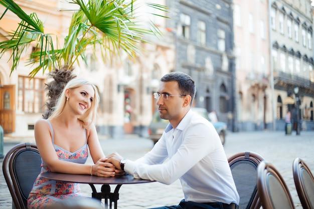 Homem de cabelos escuros em uma camisa branca com uma mulher loira em um lindo vestido