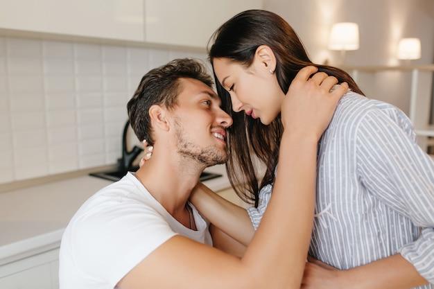 Homem de cabelos escuros feliz abraçando gentilmente a namorada e olhando nos olhos dela em um quarto com interior moderno