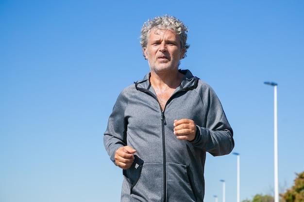 Homem de cabelos grisalhos cansado com jaqueta esporte, correndo lá fora. treinamento de corredor sênior pela manhã. vista frontal, céu azul claro, copie o espaço. conceito de atividade e idade