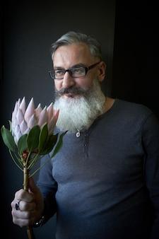 Homem de cabelos grisalhos com óculos e barba tem um protea rosa nas mãos