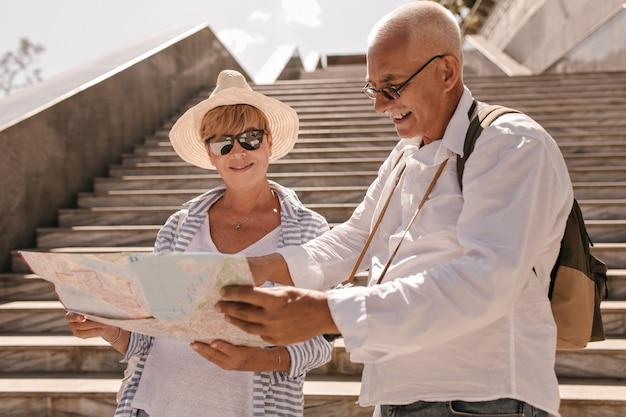 Homem de cabelos grisalhos de óculos e camisa leve com mochila olhando o mapa com uma mulher moderna de chapéu e roupas listradas azuis