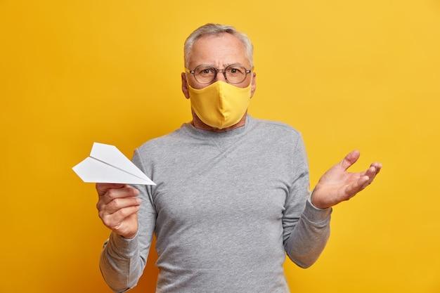 Homem de cabelos grisalhos e hesitante e perplexo levanta a palma da mão e fica confuso, usa máscara descartável para se proteger do coronavírus segura avião de papel feito à mão isolado sobre parede amarela