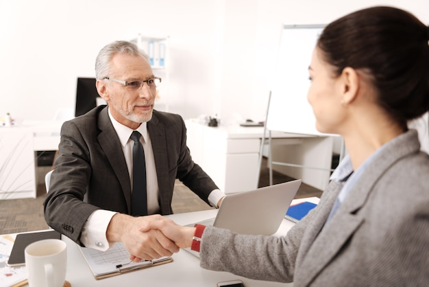 Homem de cabelos grisalhos encantado e positivo vestindo uma fantasia mantendo um sorriso no rosto enquanto está no escritório