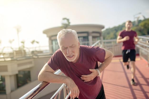 Homem de cabelos grisalhos franzindo a testa, segurando a mão no peito, jovem correndo atrás dele