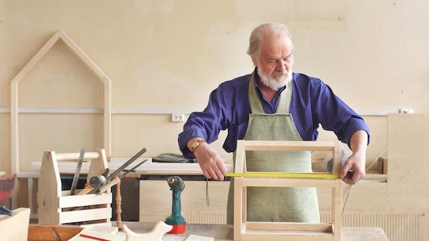 Homem de cabelos grisalhos por profissão, um carpinteiro trabalhando em sua oficina