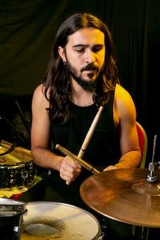 Homem de cabelos longos, tocando bateria