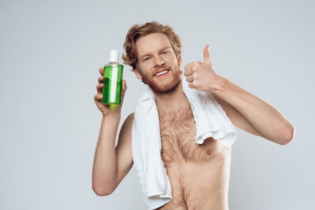 Homem de cabelos vermelho posando com uma garrafa de bochechos