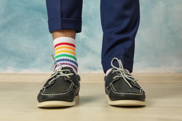 Homem de calça azul, mocassins e meias lgbt