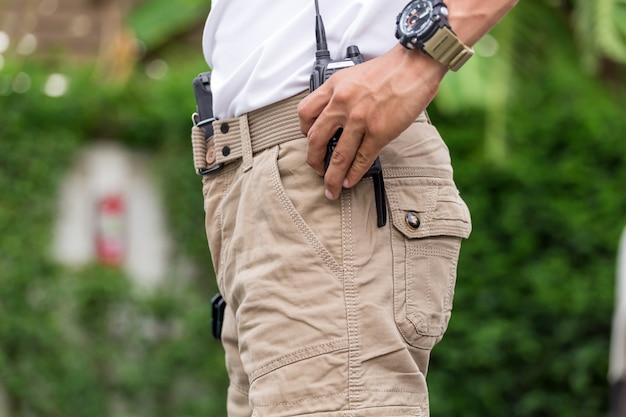 Homem de calças cargo com rádio walky talky