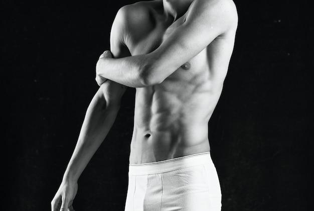 Homem de calcinha branca como corpo preto fitness posando com fundo escuro
