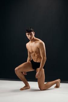 Homem de calcinha escura com corpo musculoso nu ajoelhado