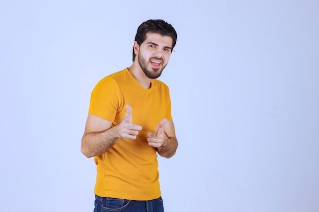 Homem de camisa amarela, apontando para alguém à frente.
