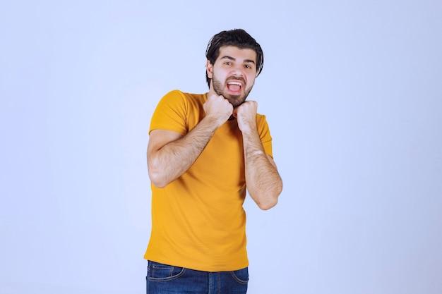 Homem de camisa amarela mostrando seu punho e força