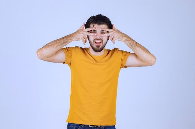 Homem de camisa amarela, olhando por entre os dedos.