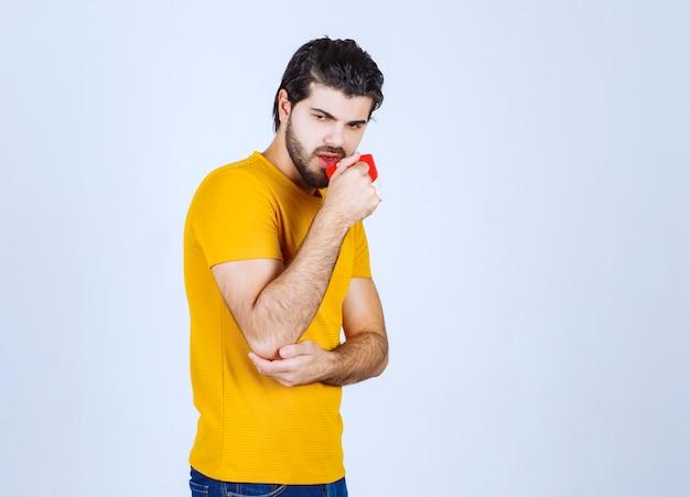 Homem de camisa amarela segurando uma xícara de café e parece misterioso.
