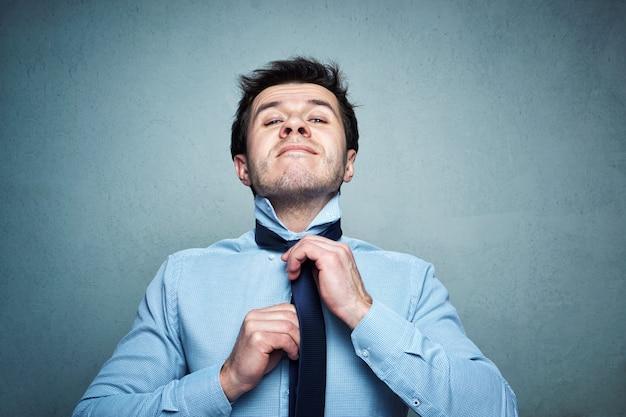 Homem de camisa amarra uma gravata com emoção sobre um fundo cinza