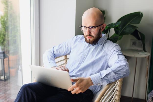 Homem de camisa azul com barba trabalhando em um laptop em casa fique em casa
