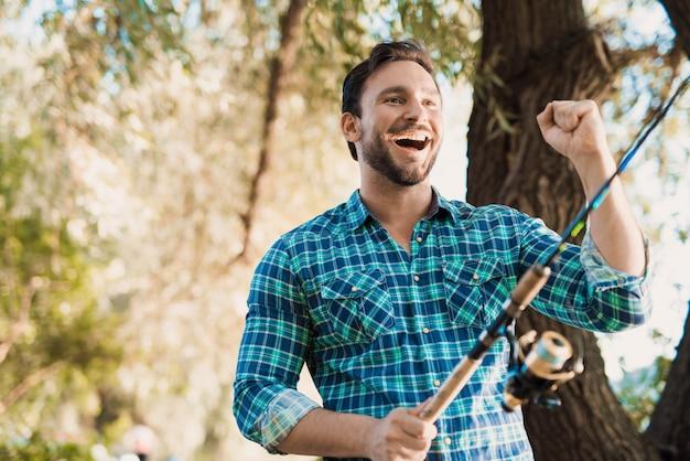 Homem de camisa azul está de pé na margem do rio e sorrindo