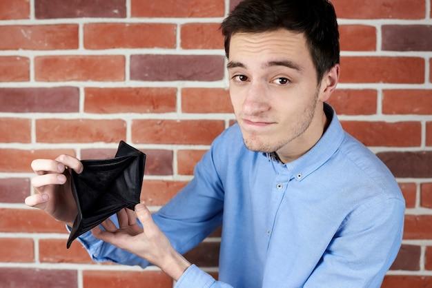 Homem de camisa azul, mostrando a carteira vazia preta